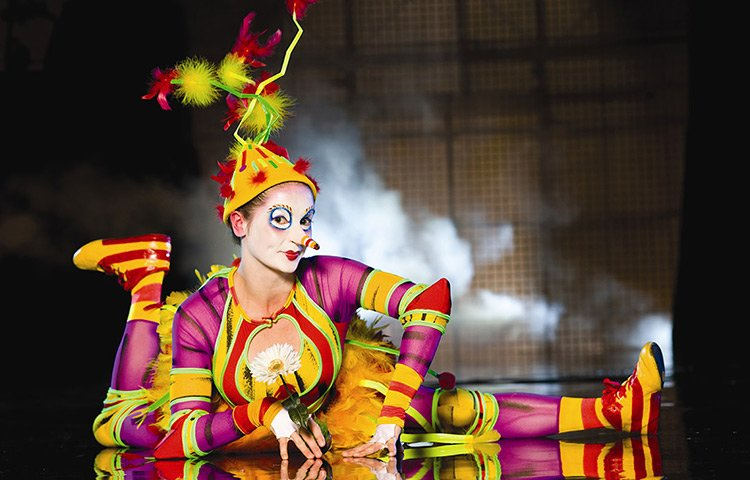 A woman lays on stage dressed in a colorful costume and makeup.