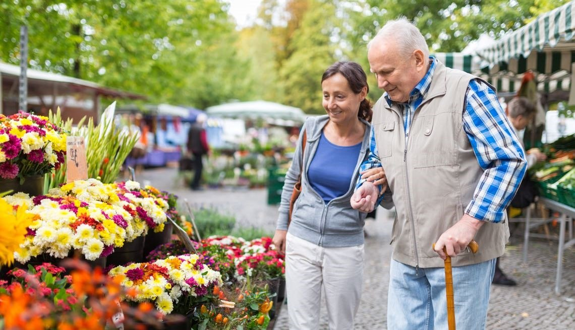 Man and woman walking by flowers at outdoor market