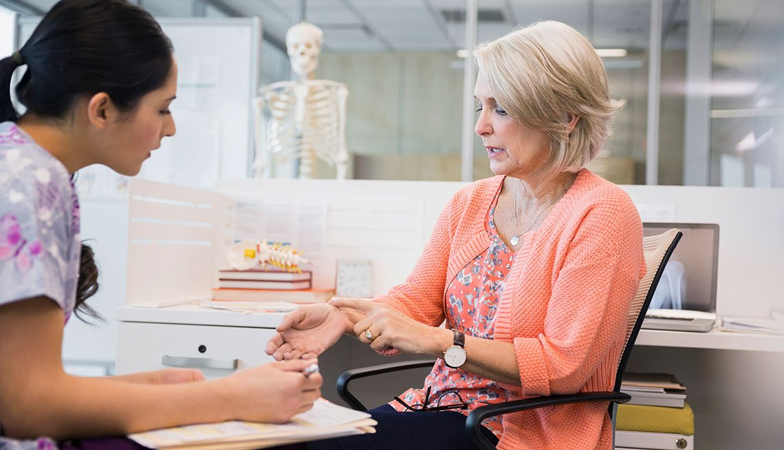 Mature Female Patient Explaining Wrist Pain in Doctor's Office, AARP Member Benefits Insurance