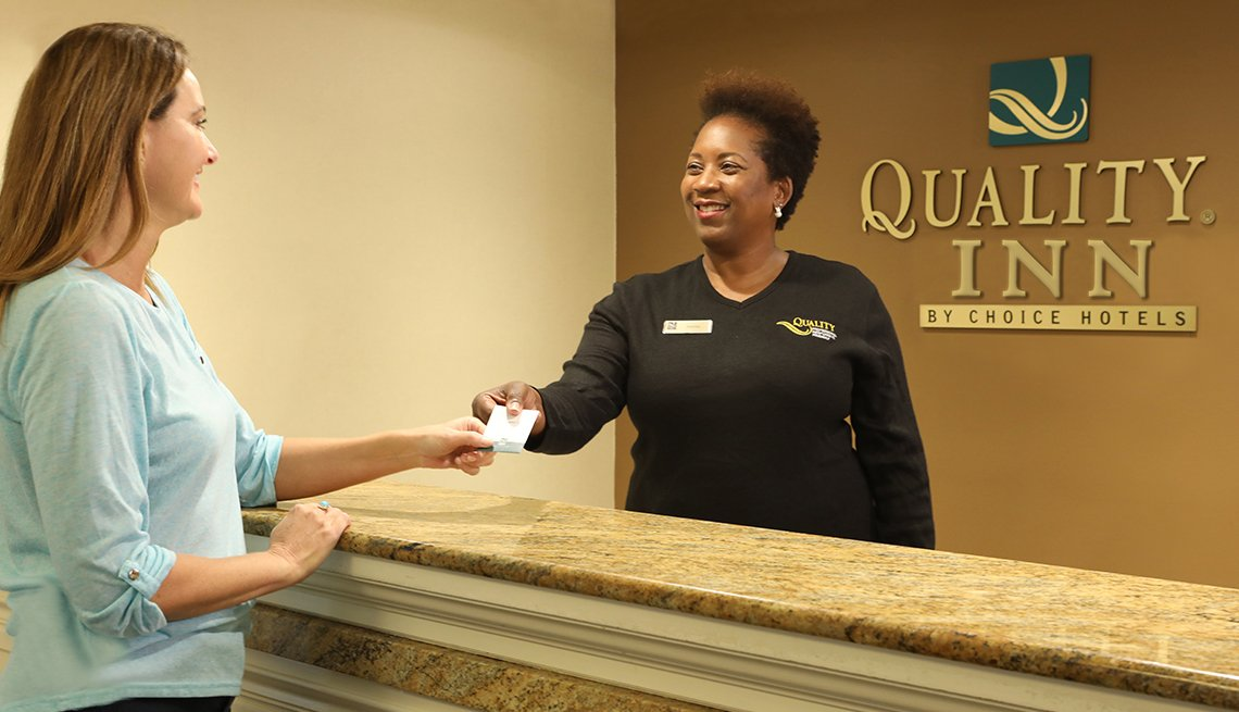 Guest and Employee at Quality Inn Front Desk, AARP Member Benefits Hotel Spotlight
