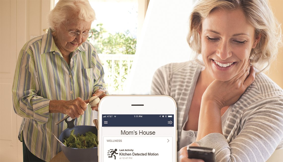Adult daughter checks mobile phone for status of elderly mom