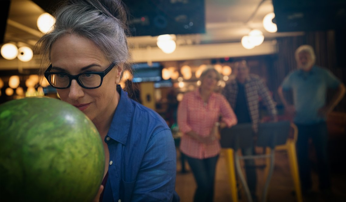 Senior Caucasian woman in glasses aims green bowling ball while others watch