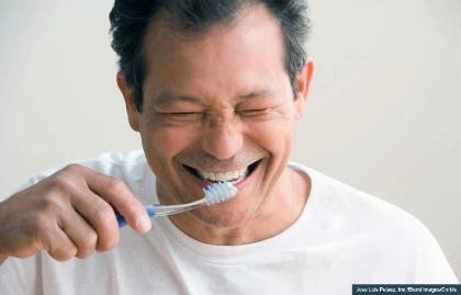 Smiling man brushing his teeth