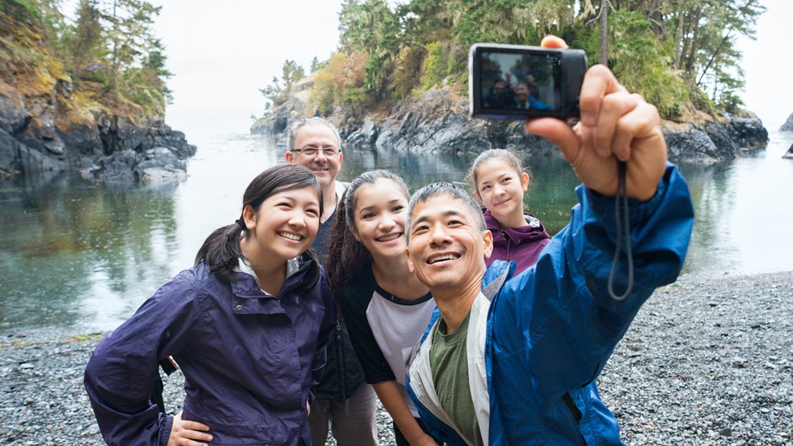 Smiling families taking a group selfie at the lake