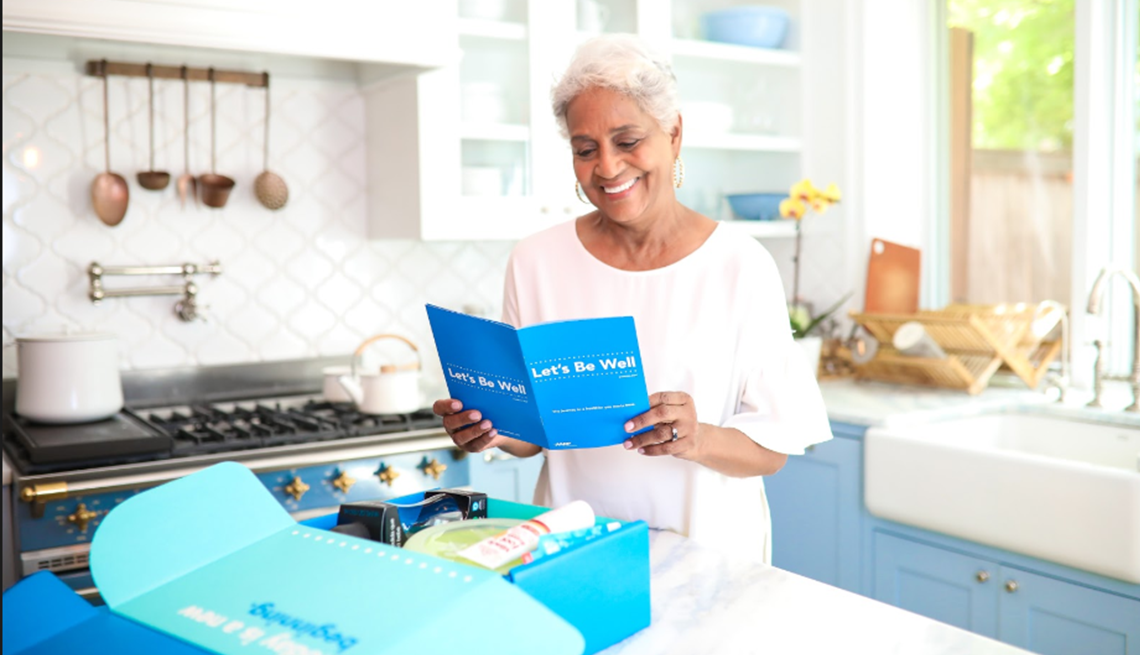 Black woman reviewing content of box in kitchen