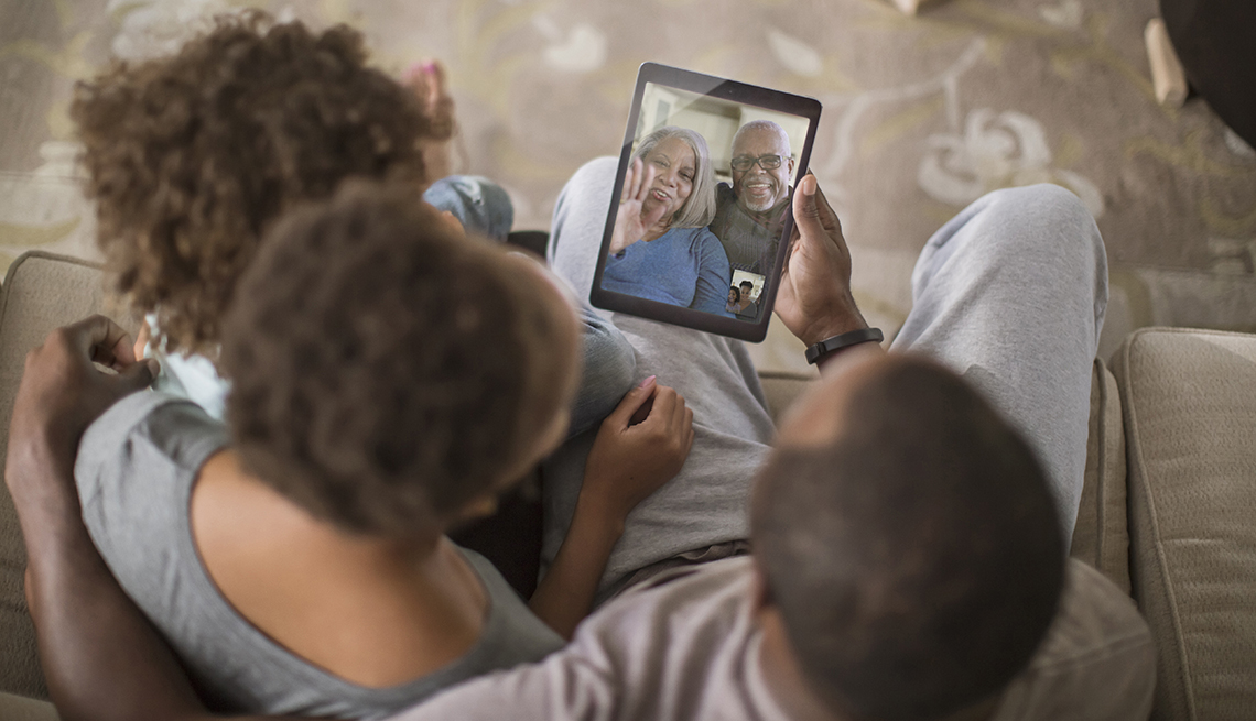 A family having a video call with their older parents