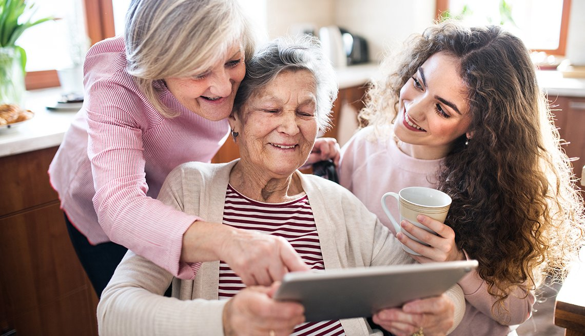 A woman with her mother, who is in a wheelchair and her teenage daughter. All are looking at a tablet together