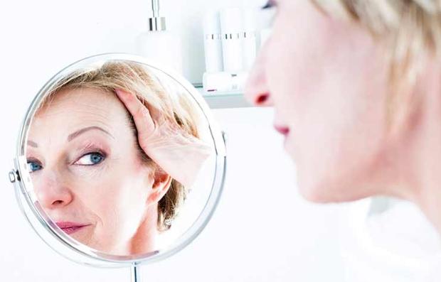 Mujer mirando su rostro en un espejo de aumento - Cremas para una piel sana y mantener un cutis joven