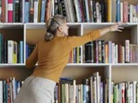 AARP Bookstore - woman reaches for book on bookshelf