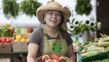 woman at farmers' market with basket of peaches