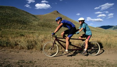 Couple riding a tandem bike together. Exercise for brain health.