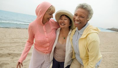 Three women laughing together on the beach.