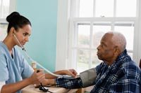 Nurse taking senior man's blood pressure