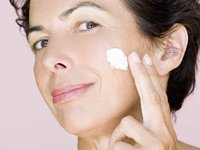 Woman applying cream to cheek. Which over the counter skin care products work best?