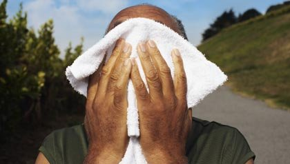 Síntomas de deshidratación - Hombre mayor limpiándose el sudor de la cara con una toalla.