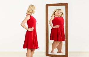 Una mujer ve su reflejo deformado en un espejo - Anorexia, bulimia - Desordenes alimenticios en las mujeres mayores