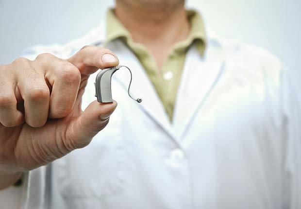 Médico sosteniendo un audífono - Cómo usar y acostumbrarse a tus nuevo audífonos