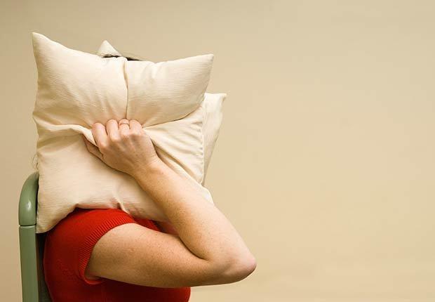 Mujer tapándose los oídos con almohadas