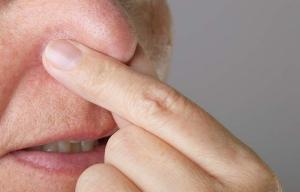 Persona tapándose la nariz