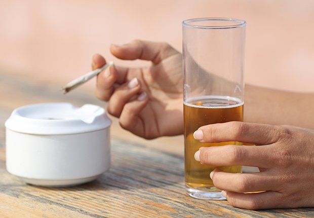Manos de una mujer sosteniendo un cigarrillo y un vaso de cerveza