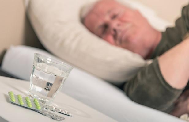 Hombre durmiendo mientras hay un vaso de agua y unas píldoras en una mesa