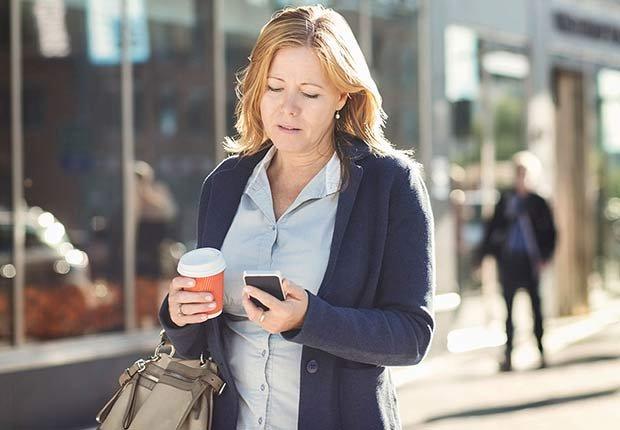 Mujer mirando su celular mientras camina por la calle