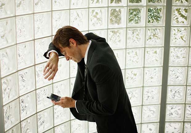 Hombre recostado de una pared utilizando su teléfono inteligente