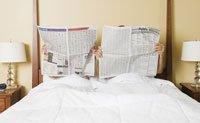 Medicamentos que pueden arruinar tu vida sexual - Pareja en la cama leyendo periódicos.