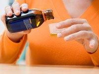 Mujer sirviendo un jarabe para la tos - Medicamentos causan tos ECA - Efectos secundarios