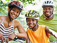 Familia en paseo en bicicleta con cascos protectores - Beneficios de la ley de salud (Obamacare) que debes saber