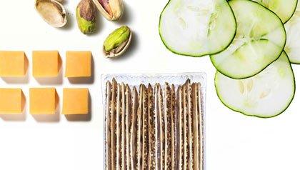 Queso, pistachos, pepinos y galletas integrales. Bocadillos saludables.
