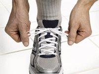 Tratamiento para la hipertensión sin medicamentos - Persona amarrándose los cordones de sus zapatos deportivos