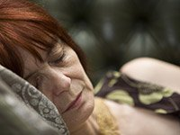 La siesta proporciona beneficios cognitivos - mujer tomando una siseta en un sofá