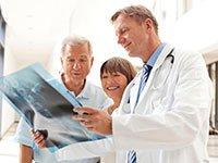 Médico revisa una imagen de rayos X con los pacientes - Hospitales mas seguros