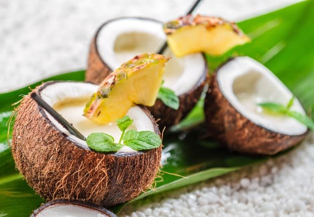 Piña colada con hojas de menta fresca servido en coco - Consejos para verse y sentirse bien este verano