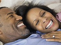 Pareja afroamericana en la cama - Razones para tener relaciones sexuales - Beneficios del sexo