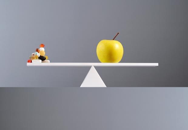Una manzana y una píldoras en una balanza - 10 Consejos saludables para perder peso este verano