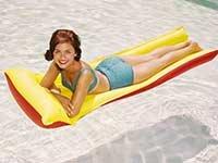 Mujer bronceándose en una piscina - Cuidado de la piel en sus años 50s, 60s o 70s