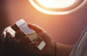 Mujer usando un teléfono inteligente en el avión durante el vuelo - Evite enfermarse mientras viaja