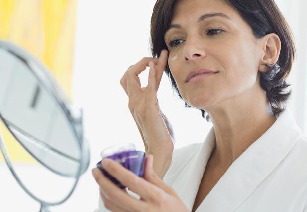 Mujer aplicándose una crema en la cara - Alimentos para una piel más joven y saludable.