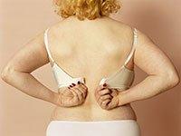 Mujer desabrochándose un sostén - Cosas que debes botar de tu casa