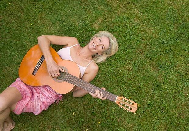 Mujer tocando guitarra - Regalos buenos para la salud