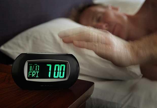 Hombre durmiendo y un despertador - Números que pueden extender tu vida