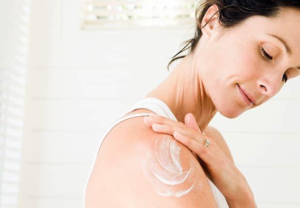 Mujer poniéndose crema en el cuerpo