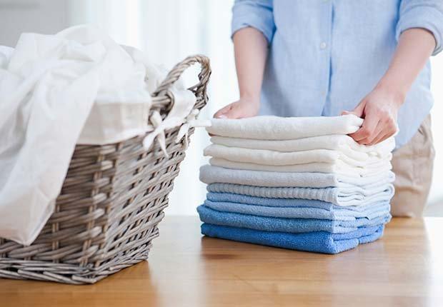 Mujer doblando ropa limpia