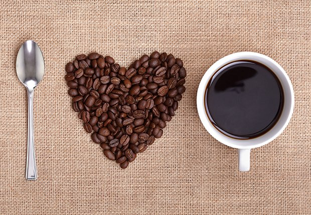 Cuchara, granos de café y taza de café