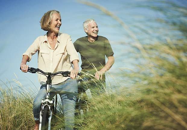 Pareja mayor montando bicicleta en el campo - La mantequilla de maní te puede hacer más saludable