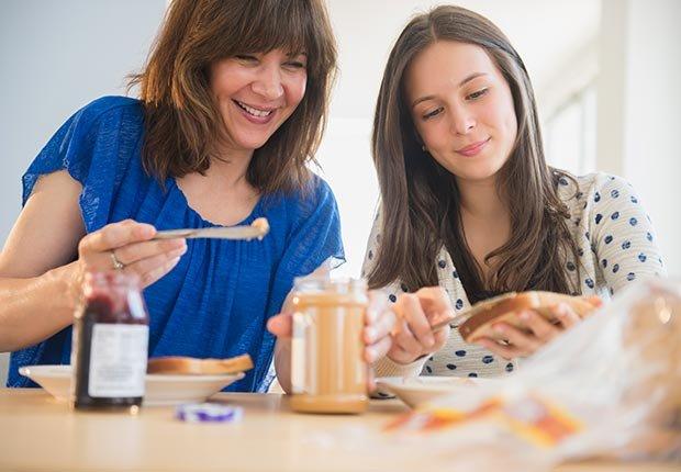 Dos mujeres untando mantequilla de maní a rebanadas de pan - La mantequilla de maní te puede hacer más saludable