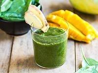 Vaso con un jugo verde decorado con rebanadas de pera - Cómo reacciona tu cuerpo ante un detox