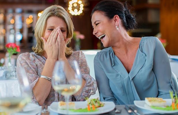 Mujeres cenando y riéndose
